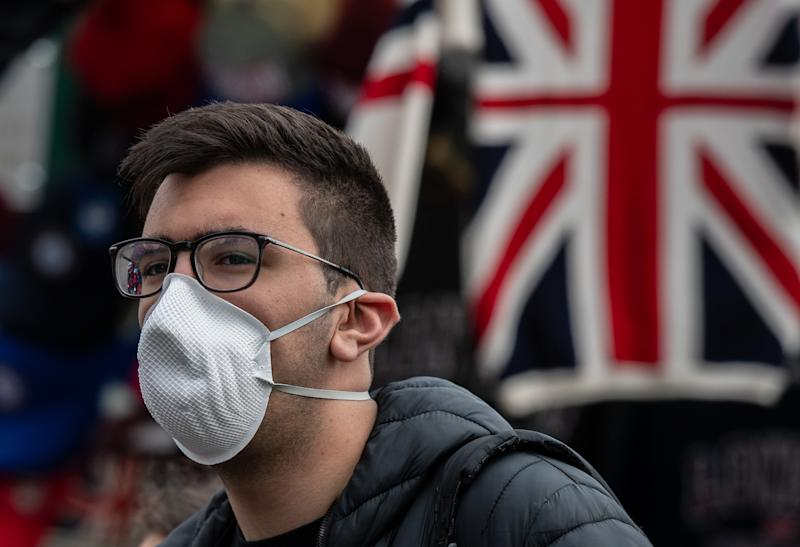 LONDON, ENGLAND - MARCH 14: A tourist wears a face mask next to a souvenir stall on Westminster Bridge as the outbreak of coronavirus intensifies on March 14, 2020 in London, England. Many Londoners and tourists are continuing they daily activities whilst mass gatherings could be banned in the UK from as early as next weekend as the outbreak of coronavirus intensifies. Many nations in Europe have already introduced strict travel bans and limits on their citizens daily lives whilst the United States has suspended incoming travel from European countries. (Photo by Chris J Ratcliffe/Getty Images)