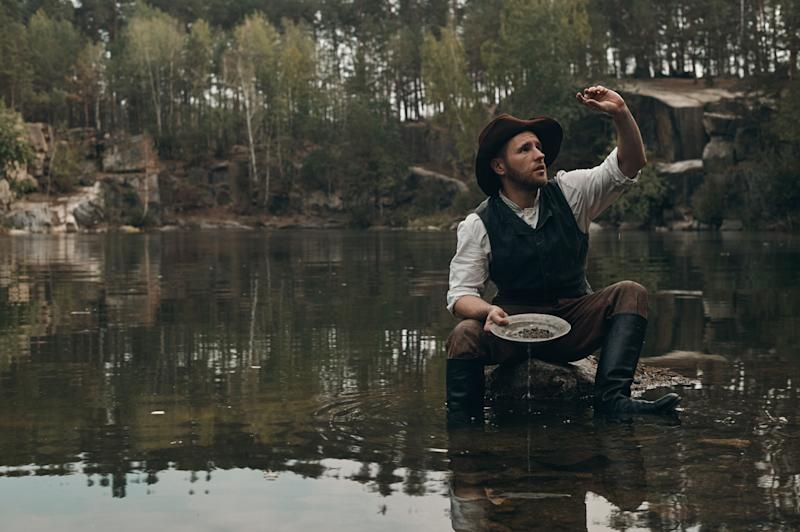 A prospector in a river panning for gold.