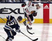 Chicago Blackhawks forward Brandon Hagel, right, controls the puck in front of Columbus Blue Jackets forward Cam Atkinson during the third period of an NHL hockey game in Columbus, Ohio, Tuesday, Feb. 23, 2021. The Blackhawks won 6-5 in a shootout. (AP Photo/Paul Vernon)