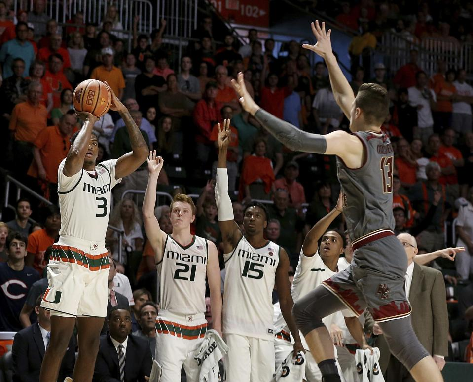 Miami's Sam Waardenburg (21) and Ebuka Izundu (15) react as guard Anthony Lawrence II, left, attempts a three-pointer against Boston College forward Luka Kraljevic, right, in the second half of an NCAA college basketball game in Coral Gables, Fla., Saturday, Feb. 24, 2018. (Pedro Portal/Miami Herald via AP)