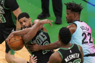 Boston Celtics' Tristan Thompson, left, grips the ball under pressure from Miami Heat's Jimmy Butler, right, as Celtics' Aaron Nesmith, center, looks on in the first half of a basketball game, Sunday, May 9, 2021, in Boston. (AP Photo/Steven Senne)
