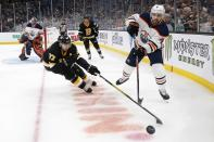 Edmonton Oilers' Kris Russell (4) plays the puck as Boston Bruins' Patrice Bergeron (37) skates in during the first period on an NHL hockey game in Boston, Saturday, Jan. 4, 2020. (AP Photo/Michael Dwyer)