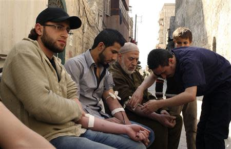 Men donate blood during a campaign to supply blood to field hospitals in Aleppo