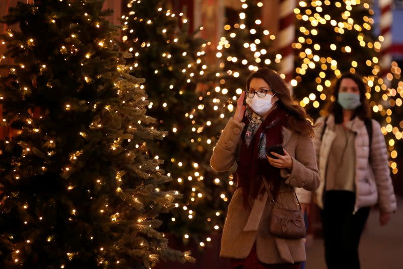 People, wearing protective face mask, walk past Christmas trees in Paris