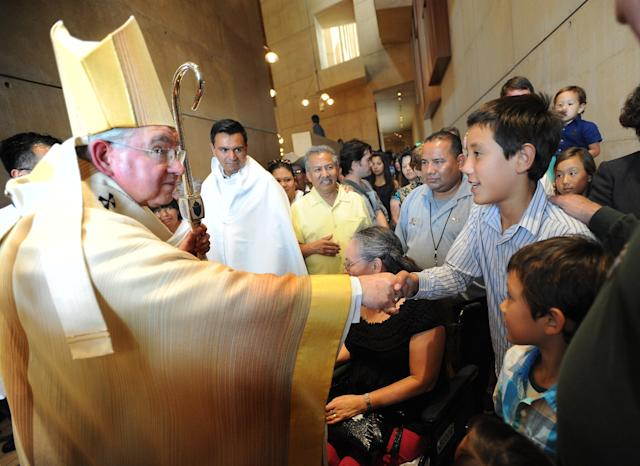 Joey Santos, 12, top right, and Matthew Santos, 7, bottom right, of Costa Mesa, Calif., meet Archbishop José H. Gomez following a mass for immigration reform at the Cathedral of Our Lady of the Angels in Los Angeles. The Santos family joined about 400 Orange County residents who attended the mass on July 21, 2013. (Photo: Ana Venegas/The Orange County Register/ZUMAPRESS.com)
