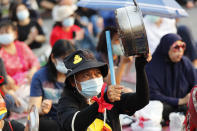 A pro-democracy protester bangs a metal pan to make noise during a rally at Democracy Monument in Bangkok, Thailand, Saturday, Feb. 13, 2021. The rally in the Thai capital was organized by the Ratsadorn movement, which campaigned last year for Prime Minister Prayuth Chan-ocha and his government to step down, the constitution to be amended and the reform of the monarchy to make it more accountable. (AP Photo/Sakchai Lalit)