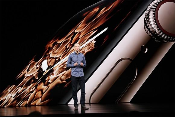 Apple COO Jeff Williams on stage in front of an image of the Apple Watch Series 4.