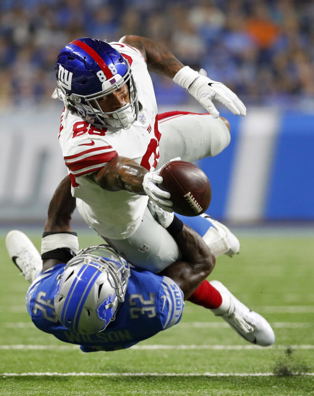 New York Giants tight end Evan Engram (88) stretches for yardage as Detroit Lions defensive back Tavon Wilson (32) tackles him during the first half of a preseason NFL football game, Friday, Aug. 17, 2018, in Detroit. (AP Photo/Paul Sancya)