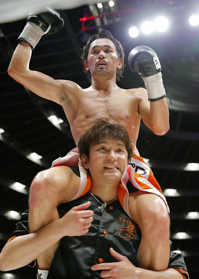 Japanese champion Shinsuke Yamanaka is carried on the shoulders of his corner's man after defeating Belgian challenger Stephane Jamoye in their WBC bantamweight boxing title bout in Osaka, western Japan, Wednesday, April 23, 2014. Yamanaka defended his title with a technical knockout in the ninth round. (AP Photo/Kyodo News)