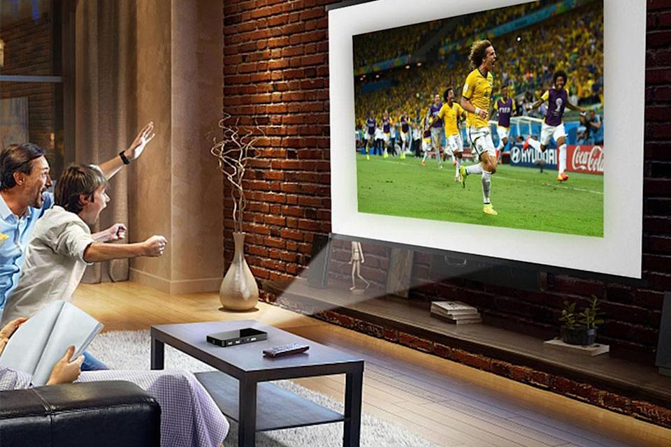 man and his son jumping up from a couch while they watch a soccer game on a projector