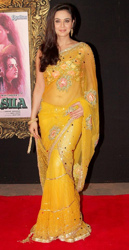 Radiating in mustard yellow, Preity's sari is fitting for a reception or an evening of cocktails.