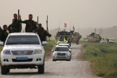Kurdish fighters from the People's Protection Units (YPG) head a convoy of U.S military vehicles in the town of Darbasiya next to the Turkish border