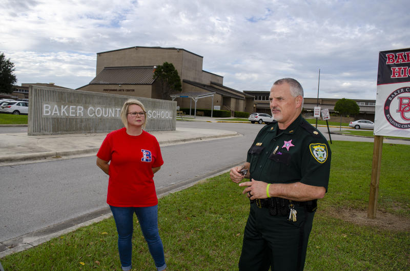 In this Oct. 16, 2019 photo, Baker County Sheriff's Maj. Randy Crews and Angela Callahan speak, outside at Baker County High School in Glen St. Mary, Fla.,  They share concern about a judge's decision to dismiss second-degree felony charges against a 15-year-old who had written a six-plan describing a massacre at the county's only high school. Each has a child attending Baker County High School. (AP Photo/Bobby Caina Calvan)