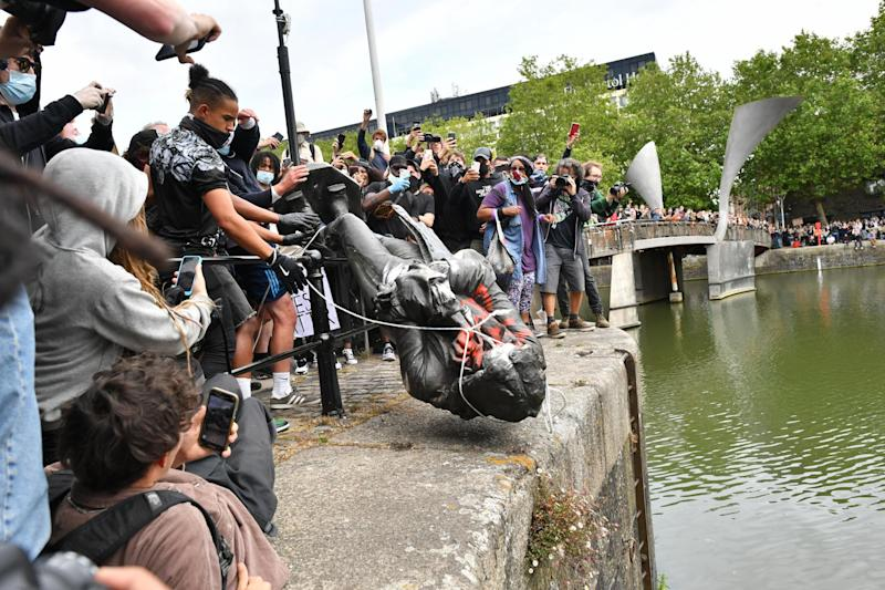 Black Lives Matter protesters throwing the controversial statue of slave trader Edward Colston into Bristol harbour in June (PA)