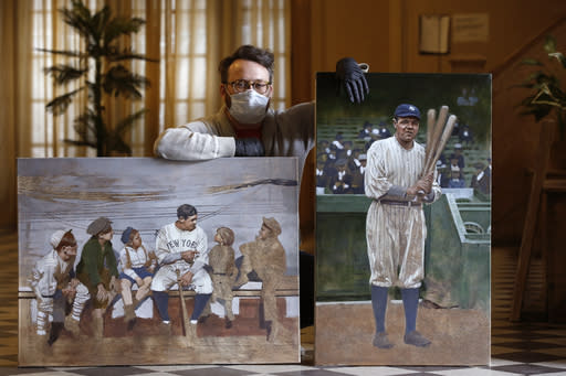 """In this Wednesday, April 29, 2020, photo, Brooklyn-based baseball artist Graig Kreindler poses with two of his paintings of Babe Ruth, both unfinished, in the lobby of his residence in New York. Over 200 of Kreindler's paintings form the bulk of the exhibit """"Black Baseball in Living Color:The Art of Graig Kreindler,"""" at the Negro Leagues Baseball Museum in Kansas City, Mo. The museum is closed now, but expects to reopen early in June. Both paintings of Ruth are based on photographs. (AP Photo/Kathy Willens)"""