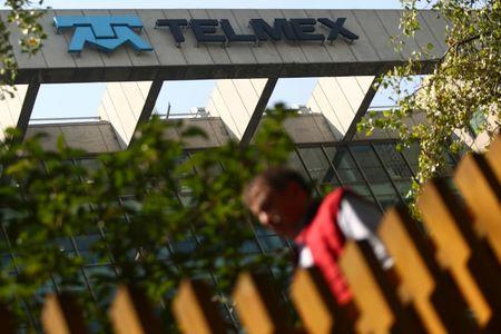 A man crosses a pedestrian bridge next to the headquarters of internet and fixed-line phone company Telmex, commercial brand of America Movil, in Mexico City