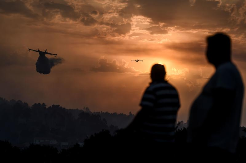 Villagers watch fire squads drop water over a wildfire as the sun sets in Chaveira in Macao in central Portugal on July 22, 2019. (Photo: Patricia De Melo Moreira/AFP/Getty Images)