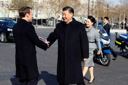 French President Emmanuel Macron greets his Chinese counterpart Xi Jinping and his wife Peng Liyuan as they arrive at the Arc de Triomphe monument to attend a wreath laying ceremony, in Paris, France March 25, 2019. Francois Mori/Pool via REUTERS