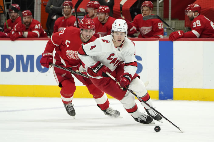 Carolina Hurricanes defenseman Haydn Fleury (4) protects the puck from Detroit Red Wings center Dylan Larkin (71) in the second period of an NHL hockey game Sunday, March 14, 2021, in Detroit. (AP Photo/Paul Sancya)