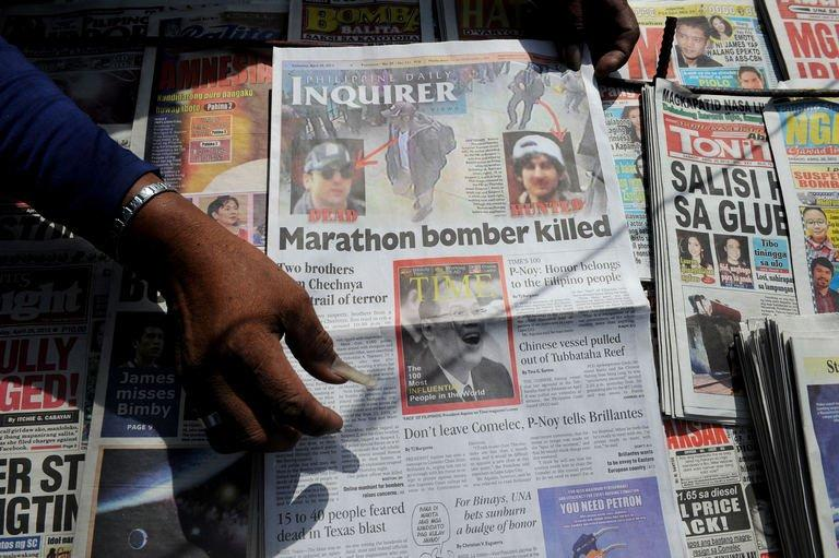 A newspaper vendor shows a local newspaper featuring a spoof Time magazine cover (C) in Manila on April 20, 2013