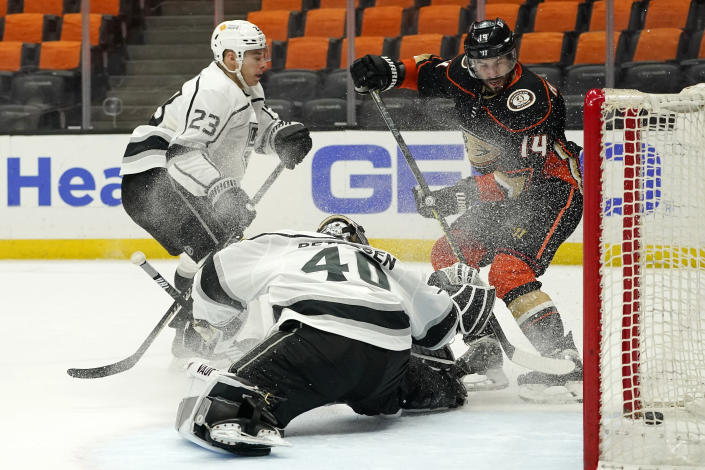 Anaheim Ducks center Adam Henrique, right, scores a game-winning goal on Los Angeles Kings goaltender Calvin Petersen, center, as right wing Dustin Brown watches during overtime in an NHL hockey game Monday, March 8, 2021, in Anaheim, Calif. The Ducks won 6-5 in overtime. (AP Photo/Mark J. Terrill)