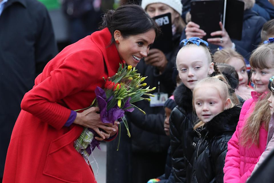 Meghan meets children during a walkabout [Photo: PA]