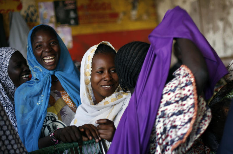 Malian women laugh as one pulls her veil saying she doesn't need it any longer in the central market in Gao, Northern Mali, Wednesday Jan. 30, 2013. The mission by French troops scored another success in its effort to dislodge the al-Qaida-linked militants from northern Mali, and freed from Islamic rule over the weekend, women started coming out wearing bright colors, makeup and jewels, after 10 month of black veils and sharia laws. (AP Photo/Jerome Delay)