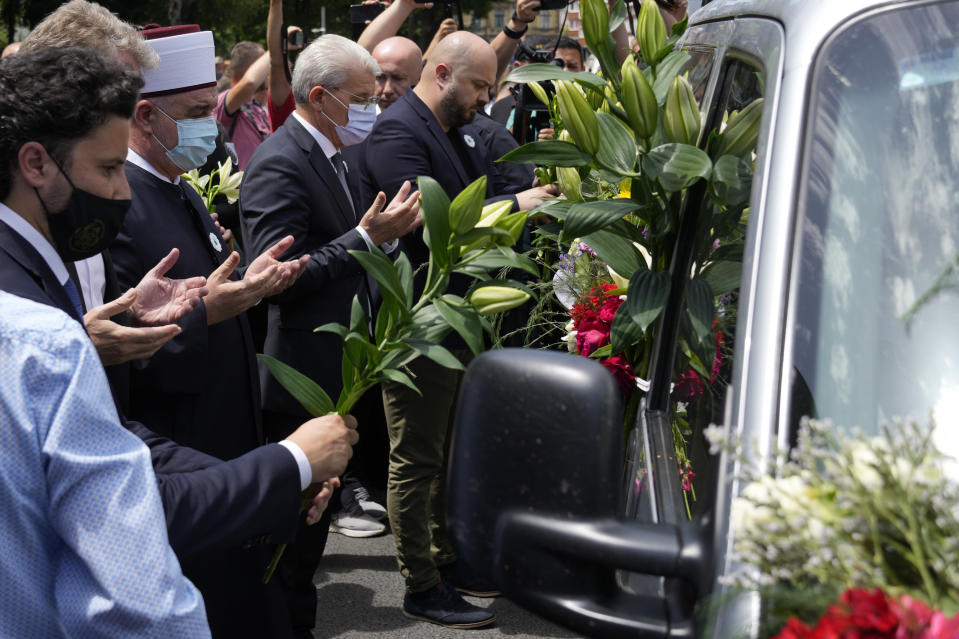FILE - In this July 9, 2021, file photo, dignitaries pay respect in front of a motorcade in Sarajevo, Bosnia, as it transport the remains of 19 victims of the Srebrenica massacre for reburial at a memorial cemetery in Srebrenica on Sunday, July 11. Twenty-six years after the July 1995 Srebrenica massacre, the only episode of Bosnia's 1992-95 war to be legally defined as genocide, its survivors continue to grapple with the horrors they endured while also confronting increasingly aggressive downplaying and even denial of their ordeal. (AP Photo/Darko Bandic, File)