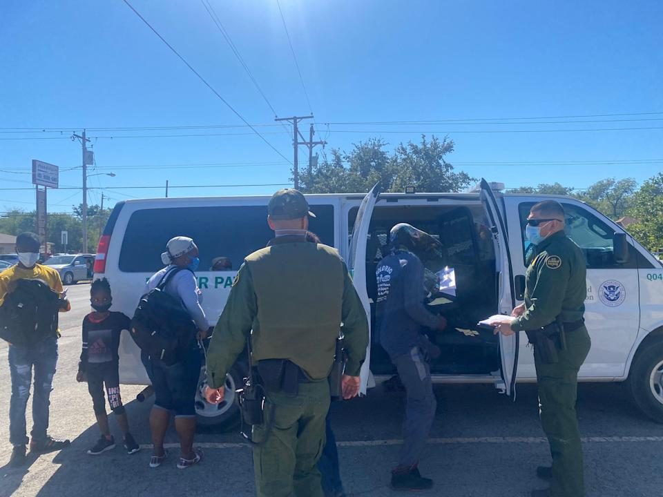 A border patrol bus drops off migrants at a transfer centre in Del Rio, Texas, after bringing them from a camp at the border. (Richard Hall / The Independent)