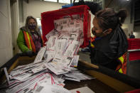 Election worker Kristen Mun from Portland empties ballots from a ballot box at the Multnomah County Elections Division, Tuesday, Nov. 3, 3030 in Portland, Ore. Oregon is the first state in the nation to institute voting by mail and automatic voter registration. (AP Photo/Paula Bronstein)