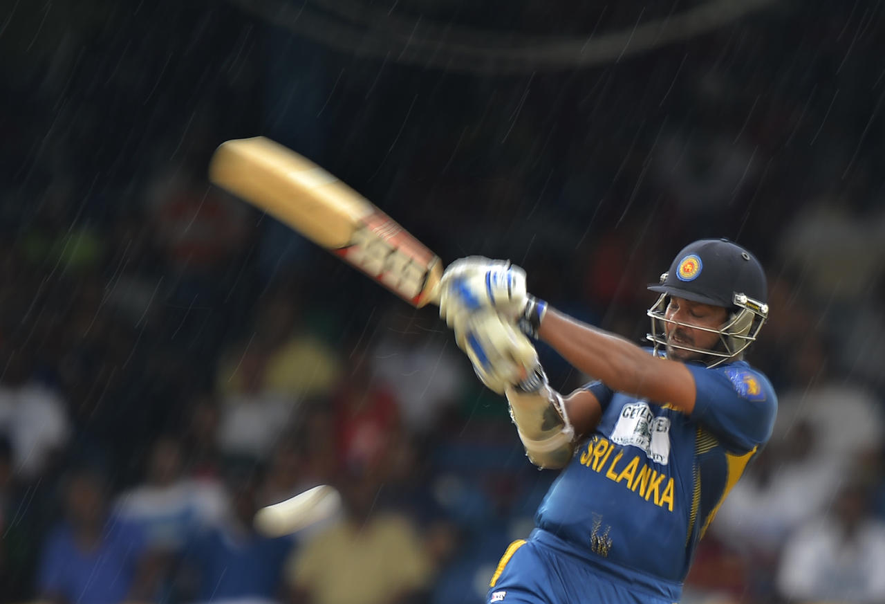 Sri Lankan cricketer Kumar Sangakkara plays a shout as rain pour during the fifth match of the Tri-Nation series between Sri Lanka and West Indies at the Queen's Park Oval in Port of Spain on July 7, 2013. West Indies won the toss and elected to field. AFP PHOTO/Jewel Samad