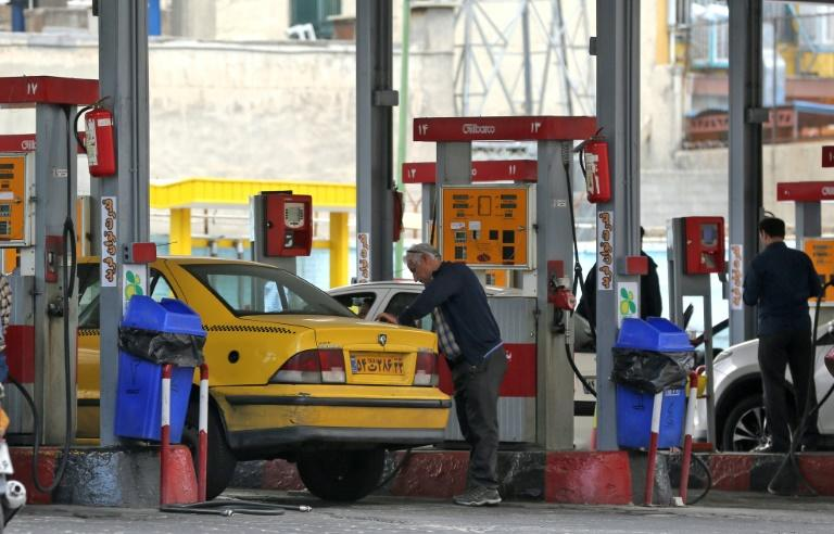 Iranian motorists fill up at a petrol station in the capital Tehran (AFP Photo/ATTA KENARE)