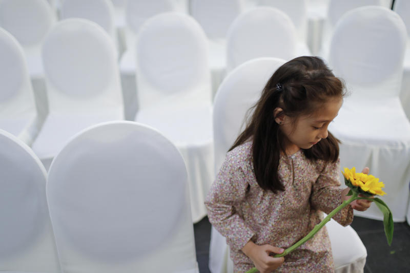 A girl holds a flower as friends and family of victims from Malaysia Airlines Flight MH17 plane crash attend a ceremony marking the fifth anniversary of the tragedy in Kuala Lumpur, Malaysia, Wednesday, July 17, 2019. Five years after a missile blew Malaysia Airlines Flight 17 out of the sky above eastern Ukraine, relatives and friends of those killed gathered Wednesday in Kuala Lumpur and at a Dutch memorial to mark the anniversary. (AP Photo/Vincent Thian)
