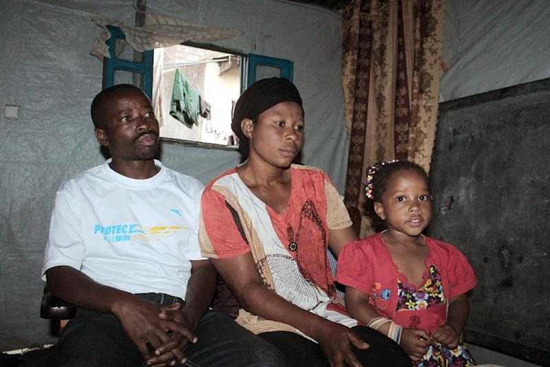 Michel, 38, a Burundian refugee, his wife Claudine, 30, and their daughter sit in their makeshift home in Goma, Democratic Republic of Congo, on March 10, 2014 (AFP Photo/Alain Wandimoyi)