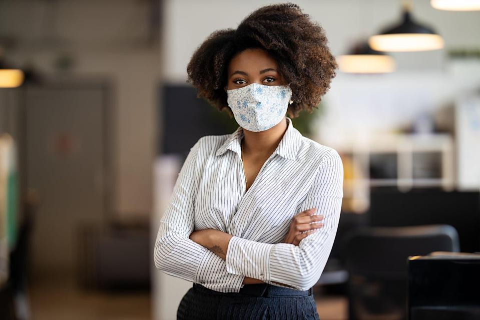 Portrait of african american businesswoman back to work at office after pandemic lockdown. Female entrepreneur with protective face mask standing alone in office with her arms crossed.