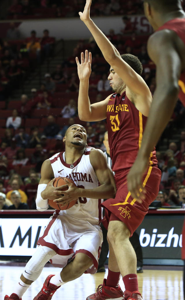 Oklahoma guard Jordan Woodard, left, eyes the basket as Iowa State guard Georges Niang, right, defends during the second half of an NCAA college basketball game in Norman, Okla., on Saturday, Jan. 11, 2014. Oklahoma won 87-82. (AP Photo/Alonzo Adams)