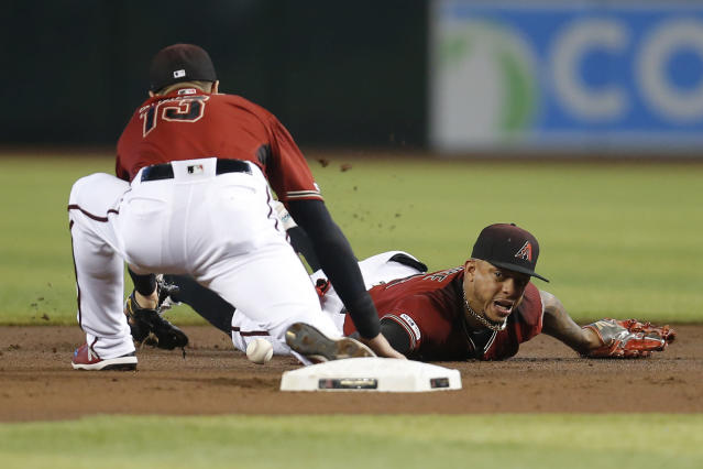 Arizona Diamondbacks second baseman Ketel Marte flips the ball to Nick Ahmed (13) for a force out on a RBI fielders choice hit by Colorado Rockies' Ryan McMahon (24) in the first inning during a baseball game, Wednesday, Aug. 21, 2019, in Phoenix. (AP Photo/Rick Scuteri)