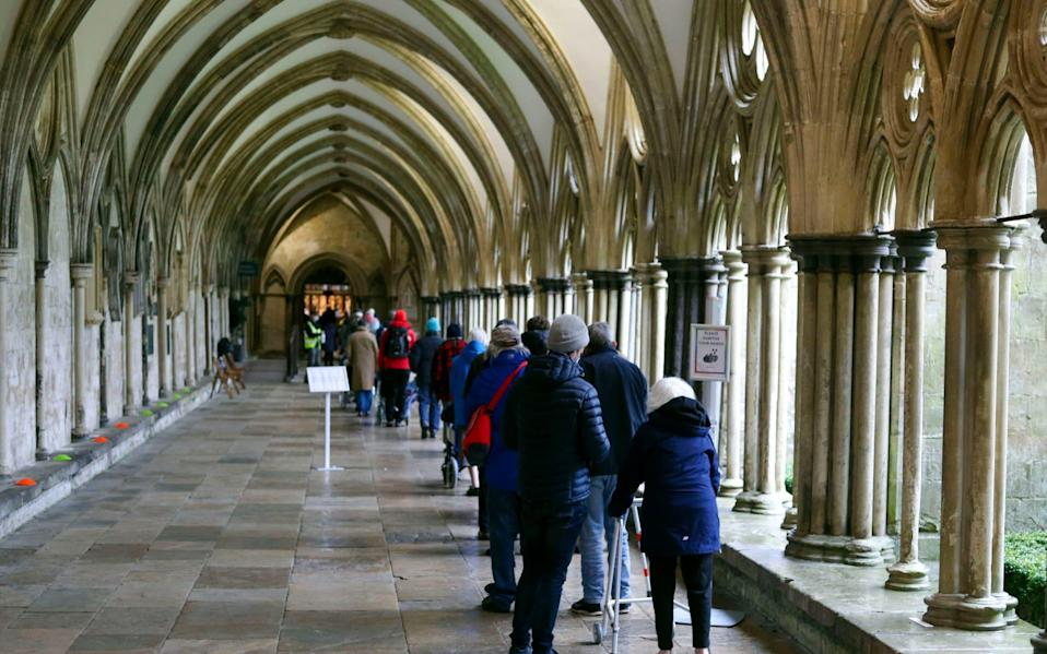 People queue outside Salisbury Cathedral, Wiltshire, to recieve an injection of the Pfizer coronavirus vaccine - PA