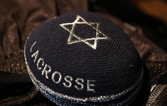 In this July 15, 2014 photo, a stack of traditional Jewish caps bear the words Israel Lacrosse inside a hotel room used for storage of the Israeli Lacrosse team's gear, in Commerce City, Colo. In its first tournament appearance, the Israeli lacrosse team is handily defeating opponents in the Lacrosse World Championship, even as its players' minds are on their homeland. (AP Photo/Brennan Linsley)