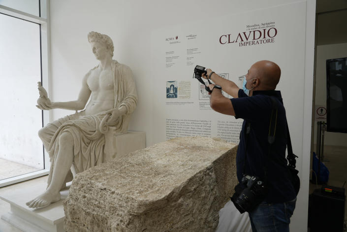 A photographer takes pictures during the presentation to the press of an archeological finding emerged during the excavations at a Mausoleum in Rome, Friday, July 16, 2021. The monumental pomerial stone is dating back to Roman Emperor Claudio and was used to mark the 'pomerium' the sacred boundaries of the 'Urbe', the city of Rome, during the Roman empire. (AP Photo/Domenico Stinellis)