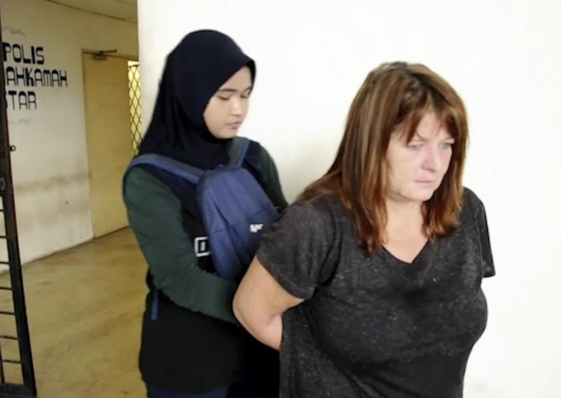 In this Thursday, Oct. 18, 2018, image from video, handcuffed British woman Samantha Jones, right, is escorted to a van at Alor Setar High Court in Kedah, Malaysia. Malaysian police said Friday, Oct. 19, 2018, that the British woman was detained on the resort island of Langkawi for allegedly stabbing her husband to death. Langkawi police chief Supt. Mohamad Iqbal Ibrahim said investigators found a 12 inch-long kitchen knife stained with blood in the couple's home where John William Jones, 62, was found dead Thursday. (StarTV via AP)