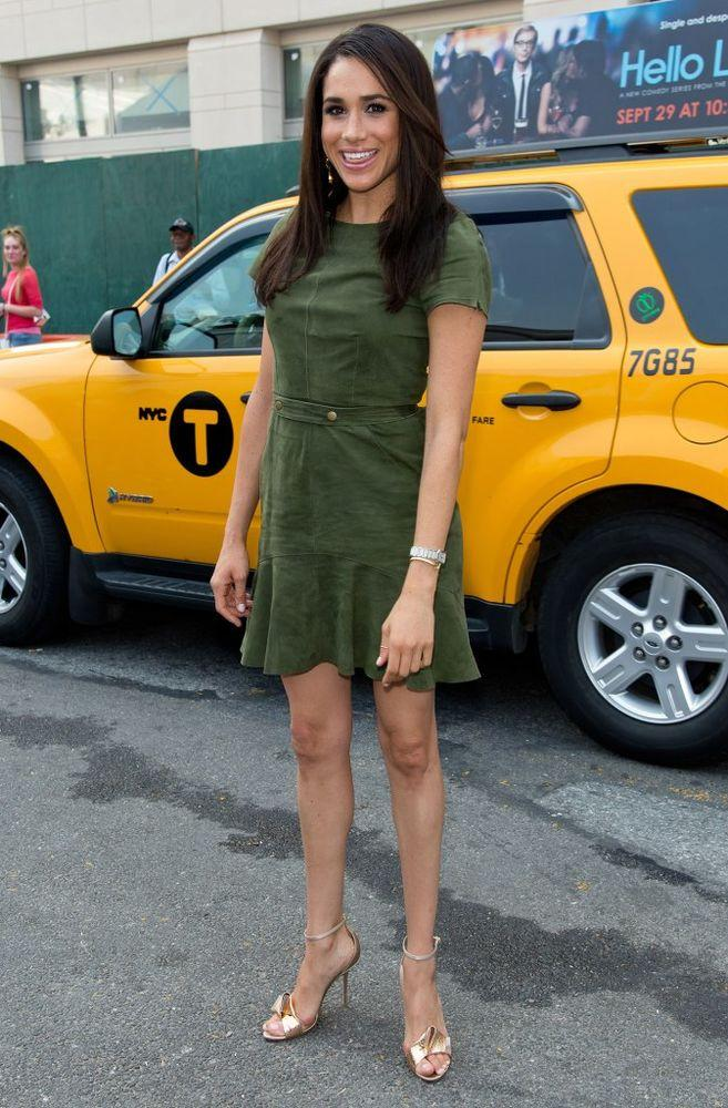 Meghan Markle in front of a yellow taxi in 2014
