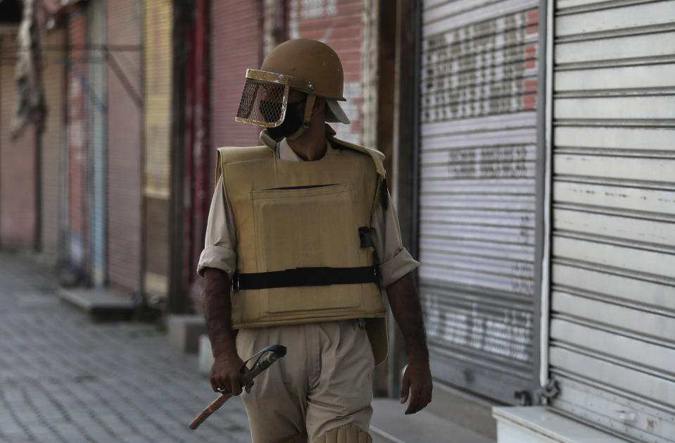 FILE- In this Thursday, Aug. 22, 2019 file photo, a Kashmiri policeman patrols outside closed shops in Srinagar, Indian-controlled Kashmir. Police in Indian-controlled Kashmir said Friday, April 16, 2021, that they arrested one of their own officers and dismissed her for obstructing a counterinsurgency operation in the disputed region. Indian law enforcement officers repeatedly have been implicated in helping Kashmiri rebels, who for decades have waged an armed campaign demanding independence for their Himalayan region or a merger with neighboring Pakistan, which administers a part of Kashmir. (AP Photo/Mukhtar Khan, File)