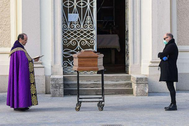 PHOTO: A man wearing a face mask stands by the coffin of his mother as a priest reads prayers during a funeral service in the closed cemetery of Seriate, near Bergamo, Italy, March 20, 2020. (Piero Cruciatti/AFP via Getty Images)