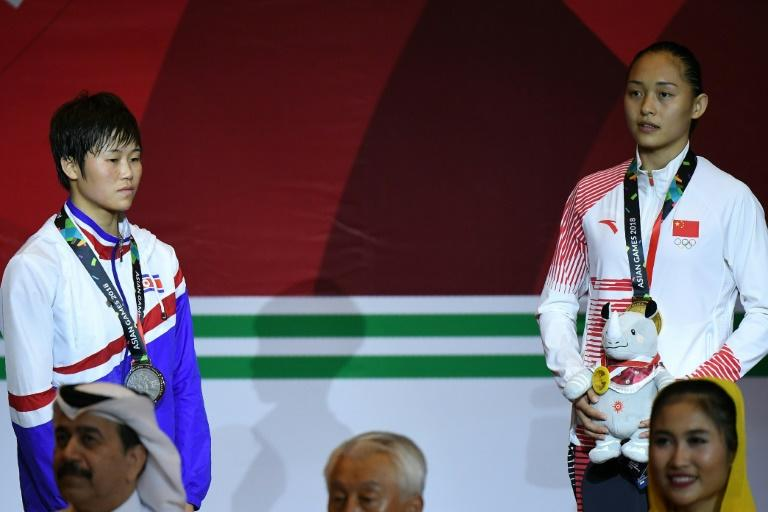 North Korea's Pang Chol Mi (left) refuses to look at the Chinese flag during the medal cermony for gold winner Chang Yuan