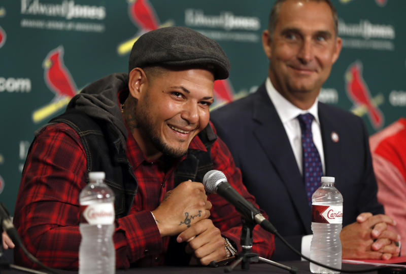 St. Louis Cardinals catcher Yadier Molina, left, smiles alongside Cardinals general manager John Mozeliak, right, during a news conference ahead of a baseball game against the Chicago Cubs, Sunday, April 2, 2017, in St. Louis. The Cardinals have finalized a contract extension with seven-time All-Star Molina that runs through the 2020 season. (AP Photo/Jeff Roberson)