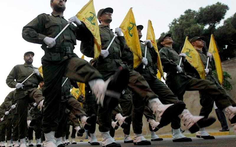 Hezbollah fighters parade during the inauguration of a new cemetery
