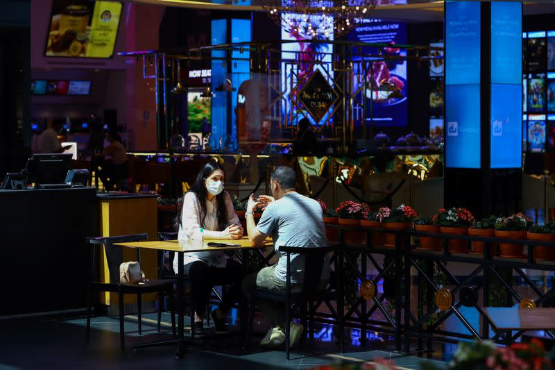 A woman wears a protective face mask as she sits with her friend in a coffee shop during the reopening of malls, following the outbreak of the coronavirus disease (COVID-19), at Mall of the Emirates in Dubai