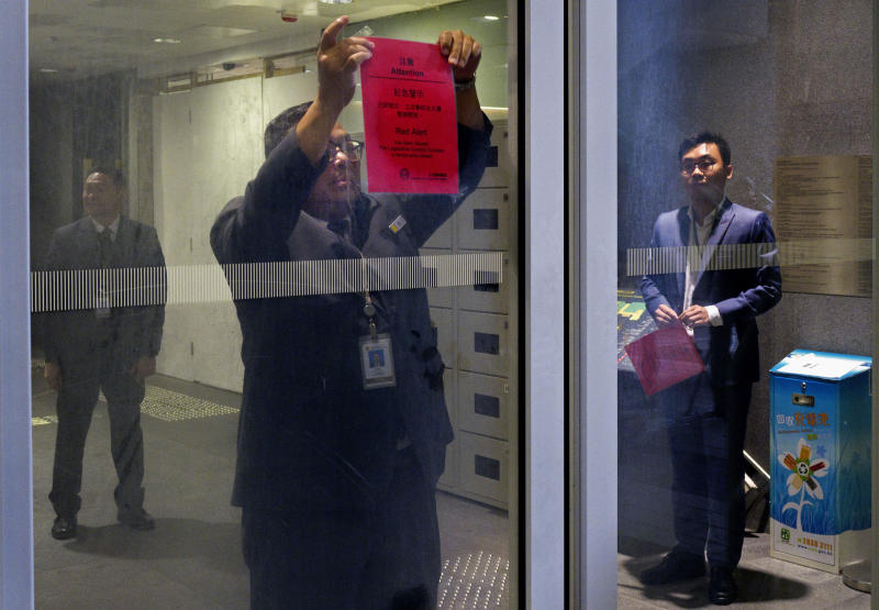 A staff tears down a red alert notice at the Legislative Council building in Hong Kong, Thursday, July 11, 2019. The red alert was pasted after hundreds of protesters swarmed into Hong Kong's legislature in the night of July 1. (AP Photo/Vincent Yu)