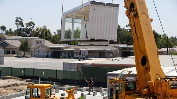 Construction workers and riggers use a crane to lift prefabricated classroom sections made of recycled shipping containers into position at Vaughn Next Century Learning Center on Friday, April 21, 2017 in San Fernando, Calif. A new project will provide upgraded classrooms on an L.A. Unified campus that hosts a charter school, replacing 21 old portable classrooms with new construction classrooms made with recycled shipping containers. (Patrick T. Fallon/ For The Los Angeles Times)